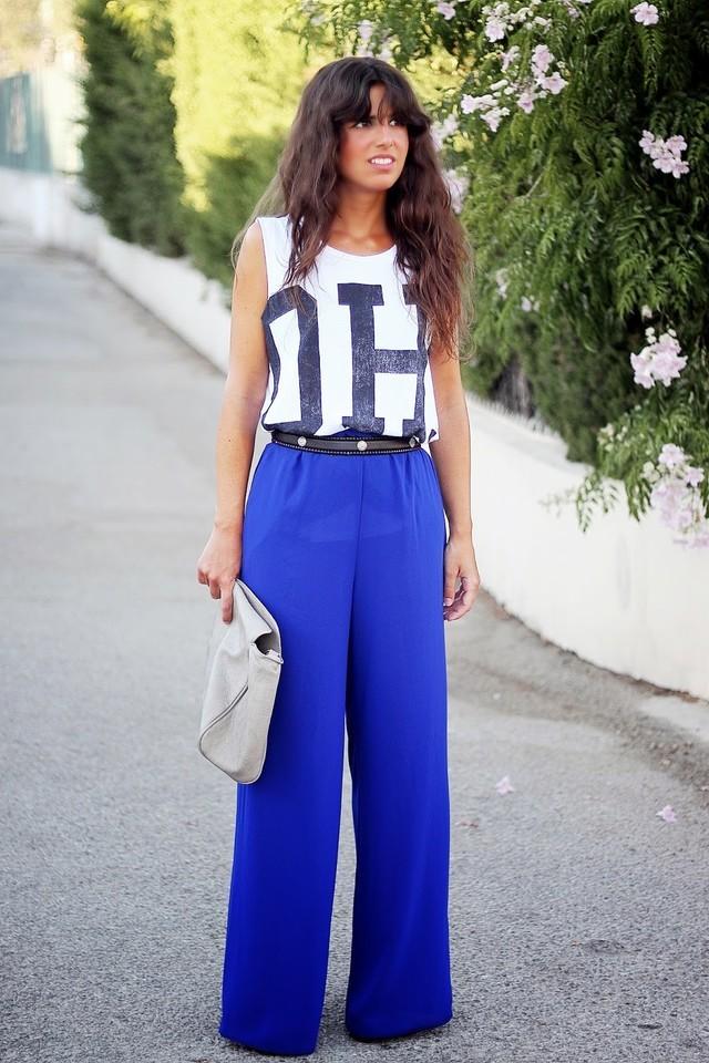 С чем носить ярко-синие брюки: широкие под майку с принтом