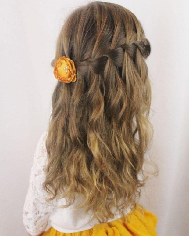 модная стрижка девочке: французский водопад вокруг головы внизу локоны украшен цветком