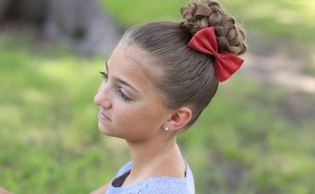 модная стрижка девочке: гулька из кос украшена бантом