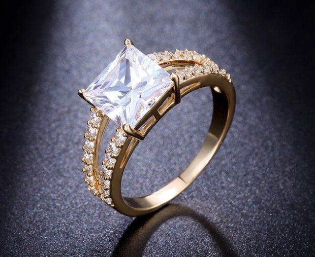 кольцо золотое с большим камнем по центру и россыпью мелких камней