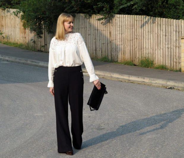 белая блуза с кружевом и темные широкие брюки