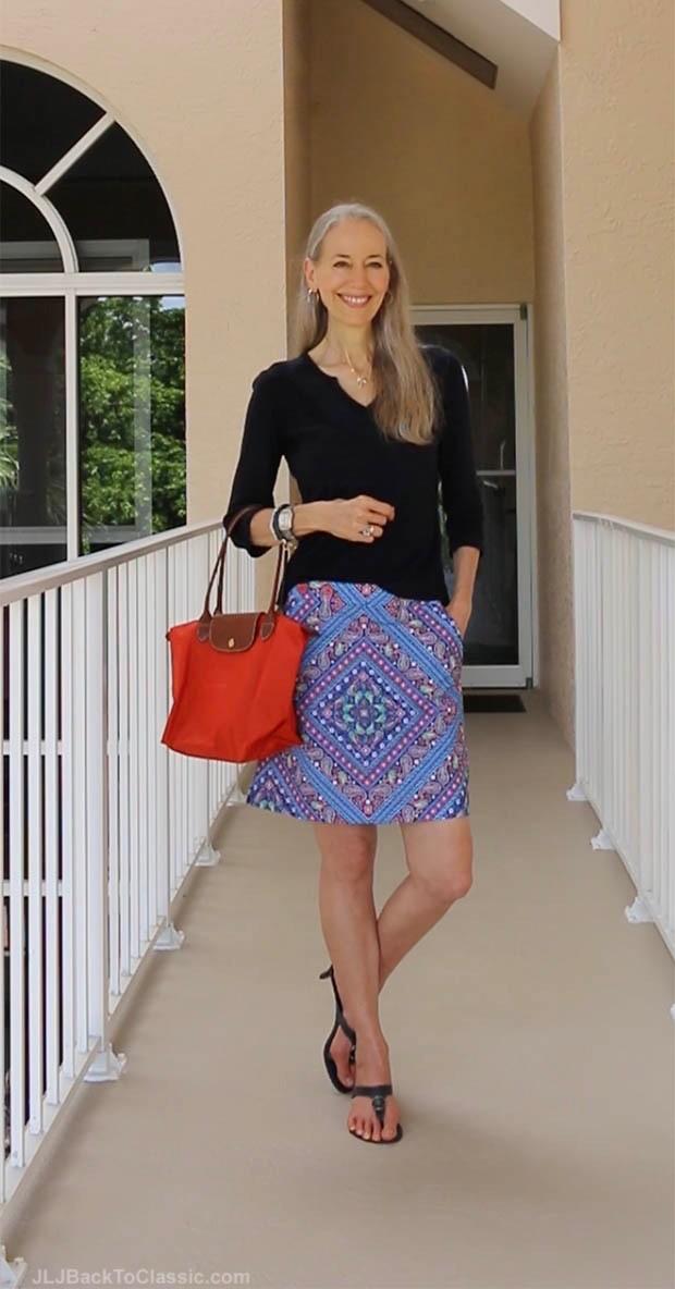 темный реглан, красная сумка и синяя юбка с принтом